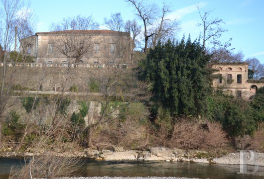 The remains of an old spinning mill and its large, luxurious home, bordered  by a river, in the French department of Gard