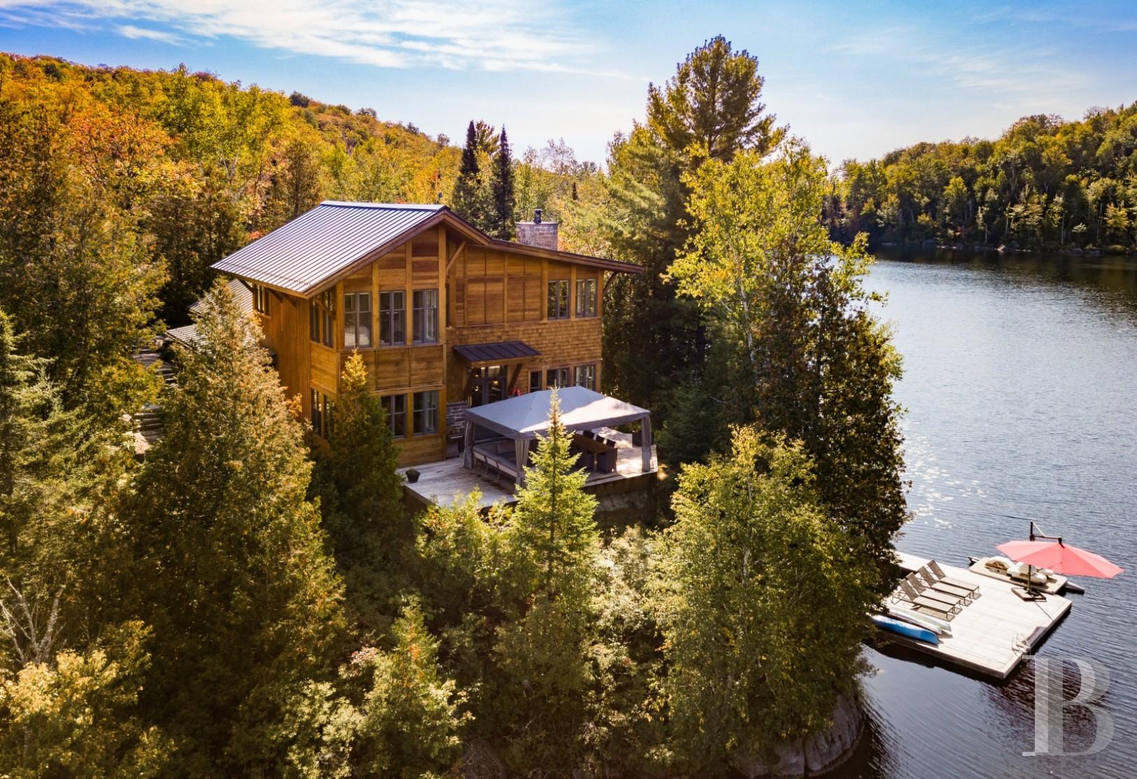 Dans les Laurentides, une élégante demeure en bois, au bord d\'un lac de  montagne